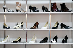 Rack of shoes in shop or department store. Many different women shoes displayed on shelves for shopping in a department store Stock Photos