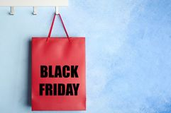 Rack with shopping bag and text BLACK FRIDAY. On color wall. Sale and special offer stock photography