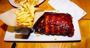Rack of spare ribs. And potato chips in chili`s restaurant stock images