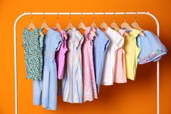 Rack with stylish child clothes. On color background royalty free stock photography