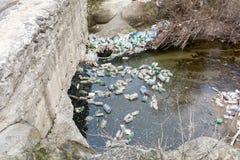 Racka ner på förorening med plast- och andra förpackande material i floden Royaltyfri Bild