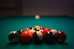 Racked and ready - Pool balls set up for play. A shallow depth of field view of racked pool balls, with the cue ball in the distance. A depiction of a common bar Stock Images