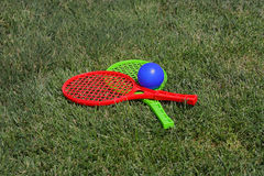 Racket and ball on green grass Stock Images