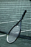 Racket on Net. Tennis racquette leaning aginst a net royalty free stock image