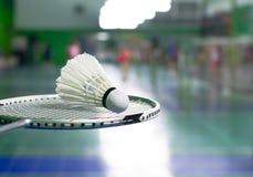 racket- och vitshuttercock över suddigt av intelligens för badmintondomstol Arkivfoto