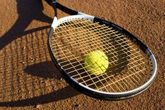 A racket and a tennis ball. Racket and tennis ball on the tennis field, nice light, warm image Royalty Free Stock Photos