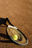 A racket and a tennis ball. Racket and tennis ball on the tennis field, nice light, warm image Stock Image
