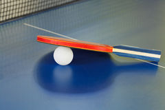 Racket, tennis ball on blue ping pong table Royalty Free Stock Images