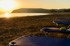 Racket and tennis balls on a chaise longue. Chair at a sandy beach during sunset stock photo