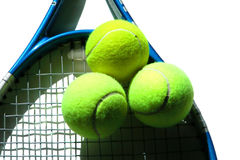 Racket with Three Tennis Balls. Blue tennis racquette with three balls resting on the strings stock photography