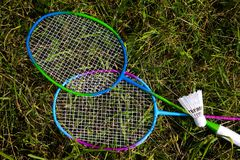 Rackets for badminton and shuttlecock lie on the grass. Sports Equipment royalty free stock photos