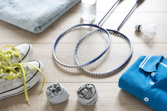 Rackets for badminton, shuttlecock, polo shirts, shoes, towel and water. Rackets for badminton, shuttlecock, polo shirts, shoes, towel and water on a wooden Royalty Free Stock Images