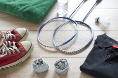 Rackets for badminton, shuttlecock, polo shirts, shoes, towel and water. Rackets for badminton, shuttlecock, polo shirts, shoes, towel and water on a wooden Stock Images