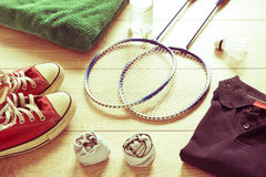 Rackets for badminton, shuttlecock, polo shirts, shoes, towel and water on a wooden floor. Retro effect Stock Photos