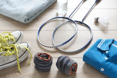 Rackets for badminton, shuttlecock, polo shirts, shoes, towel and water on a wooden floor. Retro effect Stock Images