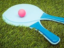 Rackets and Ball in Grass Stock Photography