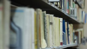 Racking Focus over Books. A short depth racking focus over a book shelf at the municipal library. A rack focus in filmmaking and television production is the stock video footage