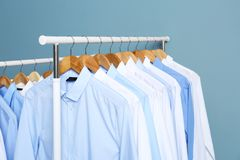 Racks with clean clothes after dry-cleaning. Against color background royalty free stock image