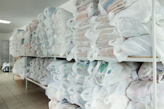 Racks with clean linen in laundry room Royalty Free Stock Images