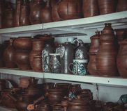 Racks in a pottery workshop with pottery, many different pottery standing on the shelves in a potery workshop. Wooden racks in a pottery workshop in which there Royalty Free Stock Image