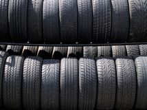 Racks/rows of tires in sunlight. Three racks of tires of varying sizes in direct sunlight Royalty Free Stock Image