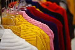 Racks of sweaters hanging in a store Royalty Free Stock Images
