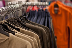Racks of sweaters and shirts hanging in a store Royalty Free Stock Photography