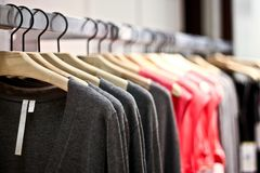 Racks of sweaters and shirts hanging in a store Royalty Free Stock Images