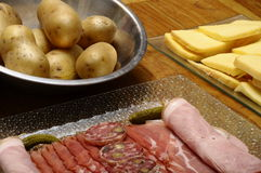 Raclette cheese with meats (ham, sausage) and potatoes Stock Photo