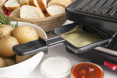Raclette cheese set. With grill and vegetables Royalty Free Stock Photo