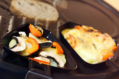 Raclette, een Zwitserse gastronomische maaltijd Stock Foto