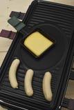 Raclette hoogste-lijst met worsten en kaas op een dienblad Stock Foto's