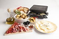 Raclette ostuppsättning på vit bakgrund med kött och korvar Arkivbild