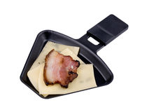 Raclette pan with cheese and bacon on white Royalty Free Stock Images