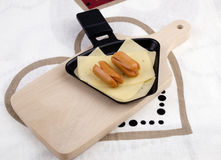 Raclette pan with cheese and sausages - party food Stock Photography