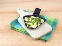 Raclette pan with cheese and spring onion Royalty Free Stock Photos