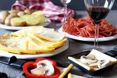 Raclette parti: ost, potatis, kött och vin fotografering för bildbyråer