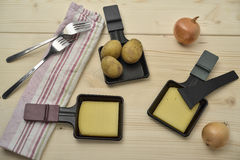 Raclette setup on a wooden table. Royalty Free Stock Photo