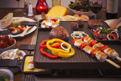 Raclette table-top grill or the Dutch variant 'gourmetten'. Swiss raclette or the Dutch variant 'gourmetten'. A table filled with ingredients for a dish that is Royalty Free Stock Photos