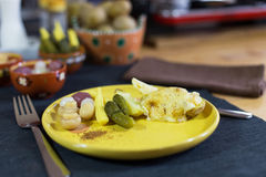 Raclette. Traditional specialty of grilled yellow cheese, potatoes and pickles Stock Photos