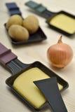 Raclettedienbladen met chessee, ui en aardappels Stock Foto's