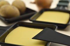Raclettedienbladen met gesmolten kaas en aardappels Stock Foto's