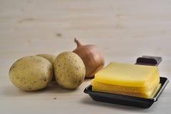 Raclettedienbladen met kaas, aardappels en ui Royalty-vrije Stock Foto