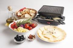 Raclettekaas met groenten op witte achtergrond wordt geplaatst die Stock Afbeelding