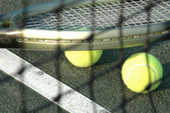 Racquet and balls through the net Royalty Free Stock Photography