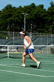Racquet Slam. Young lady playing tennis is racing toward the tennis ball Stock Photo