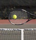 Racquet with tennis ball on court. Hit Stock Photos