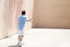 Racquetball Player. Mid adult man playing racquetball on a hot day Royalty Free Stock Photo