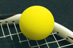 Racquetball on racket strings. Yellow frontenis ball laying on r. Acket strings, over black background Stock Image