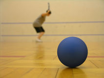Racquetball Still Life. Blue racquetball in the foreground with a player in the background Stock Photos